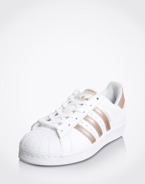 Der ´Superstar´ von Adidas Originals ist Legende. Sein Blatt ist so typisch wie seine Linienführung. Retro und dennoch immer aktuell. Das Modell wird durch Streifen im Metallic-Look vollendet.