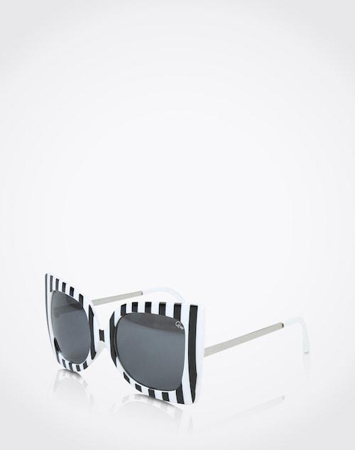 Stylisch durch den Sommer mit der Sonnenbrille ´Phebe´ von Quay. Die große, eckige Form und der schwarz/weiß Look garantieren Aufmerksamkeit am Strand.