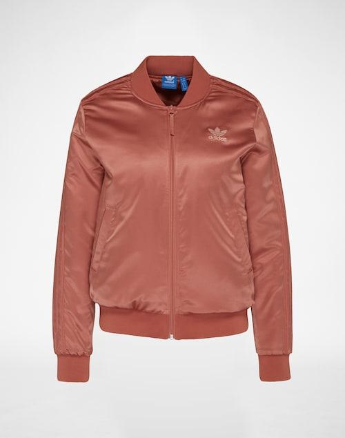 Wattierte Bomberjacke aus Satin-Qualität von Adidas Originals. Mit Rippenbündchen an den Abschlüssen und Frontzipper entsteht ein cooler Look, der durch den markentypischen Logo-Print am Rücken akzentuiert wird.